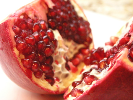 Split open the pomegranate, pulling apart the sections